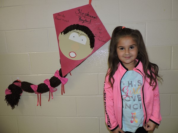 Student poses with her reading fair project, a kite.